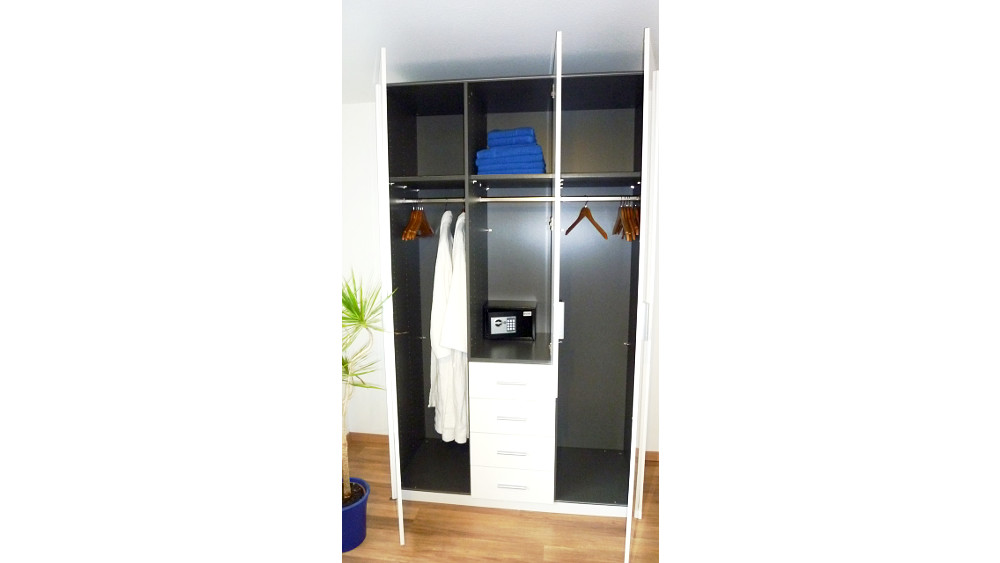Wardrobe with coat hangers and safe